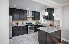 contemporary j shaped kitchen with dark cabinets and light granite countertops