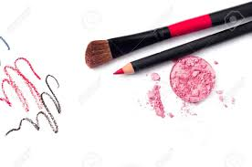 still life of a small makeup kit light tender pink eyeshadow red lip pencil