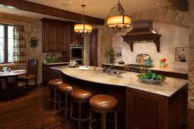 Old World Kitchen Featuring Dark Cabinetry And Contrasting Stone  Countertops, As Well As Exposed Beams