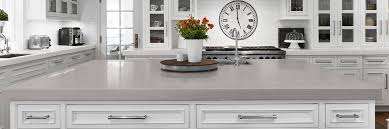 photo of a beautiful kitchen with white shaker style cabinets and gray quartz countertops
