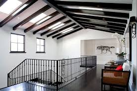 second floor hallway in a spanish revival home with exposed painted black beams black white home office cococozy 5