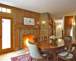 classic dining room with a tile fireplace surround oak wall and trim wooden dining room sets