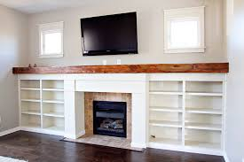 custom fireplace surround bookshelves reclaimed wood mantle window trim and tv mounting for