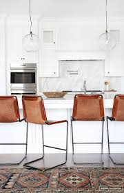 living room mid century bar stools on a vine kilim rug in an open plan all white brown leather