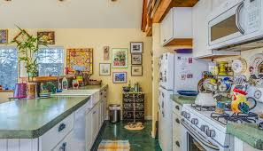 kitchen with white cabinets white appliances green laminate countertop yellow painted walls and