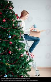 Decorating Christmas Tree With Balls Young Girl Decorating Christmas Tree With Ball At Home A Royalty 70