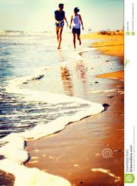 Happy Couple Playing On The Seashore At Sunset Stock Photo Image