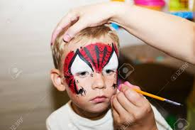 master making aqua makeup on boys face party face painting kids stock