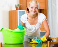 dusting furniture. Smiling Young Blonde In Rubber Gloves Dusting Furniture Living Room Stock Photo - 48984630 N