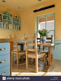 Yellow And Blue Kitchen Wooden Table Chairs In Yellow Country Kitchen With Blue Dado Stock