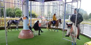 the fairground style ride was founds at the shunagliu wanda plaza ping centre in the city of chengdu and shows four horses harnessed to metal frames