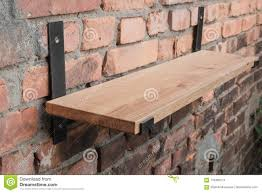 shelf in wood and metal hanging on a brick wall in loft style