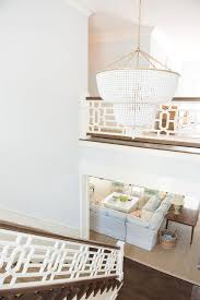 aerin jacqueline white chandelier illuminates a white fretwork staircase in a two story foyer