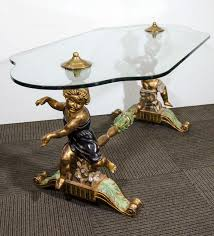 an italian hand carved coffee or cocktail table with putti or cherubs and glass