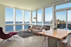 the top floor living room of this home high over alki beach has a ship