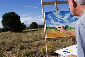 man painting picture in field
