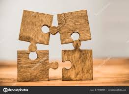 four wooden puzzle pieces wooden background concept connection people stock photo