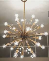 a large contemporary sputnik chandelier in brass with spiked centre and 24 arms produced in mid century style