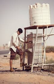 alpha mens fashion editorial photoshoot in the desert dubai middle east male model in the desert heat with a water tower backdrop