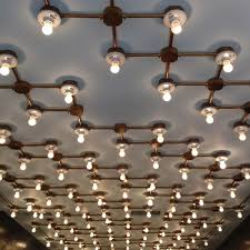 the custom lighting system in the main showroom a geometric maze of copper pipes and ceramic sockets