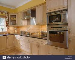 Orange And Yellow Kitchen Eye Level Oven And Microwave In Modern Yellow Kitchen With Pale
