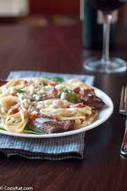 steak on top of a bed of alfredo sauce and pasta