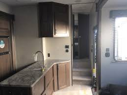 enternment center with flat screen tv and furrion sound system loft bunk leather sofa and toy hauler with electric bed p through dinette