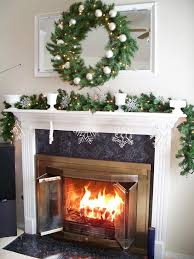 Love the greenery, white bulbs and snowflake ornaments. Gorgeous fireplace  mantle decorating ideas-