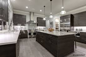 modern gray kitchen features dark gray flat front cabinets paired with white quartz countertops and a glossy gray linear tile backsplash northwest usa