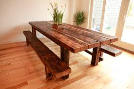 diy solid wood farmhouse kitchen table with flower centerpieces and 2 bench seats on hardwood floor tiles for dining room with white wall interior color