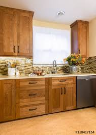 contemporary upscale home kitchen interior with cherry wood cabinets quartz countertops sustainable recycled floors