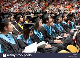 high school seniors in caps and gowns sitting in a row wait to high school seniors in caps and gowns sitting in a row wait to receive their diplomas