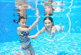 Happy Children Swim In Pool Underwater Girls Swimming Playing