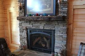 shabby and reclaimed wood mantel installed over a rustic style fireplace