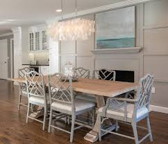 amazing dining room features a west elm large rectangle hanging capiz chandelier illuminating a salvaged wood trestle dining table lined with gray bamboo