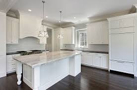 white kitchen with white subway tiles large island granite counters and drum pendant lights