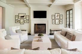 white living room with tv over fireplace