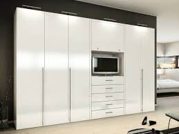 large white wooden tall narrow wardrobe with drawer under tv stand on cream laminated wooden floor bedroom bedroom closet furniture