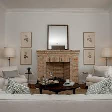 stacked art flanking brick fireplace view full size chic living room features a faded red