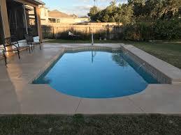new fiberglass pool with custom waterfall brick pavers and screen enclosure built in lake city fl