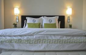 polished nickel wall sconces ivory tufted storage bench spring green pillows green monogrammed shams and white hotel duvet with green greek key trim