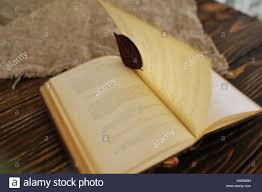 an old book with a leaf instead of a bookmark on a wooden background