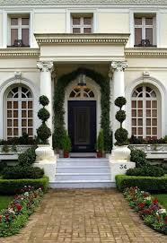 marble steps lead to an intricately carved front door framed by greenery