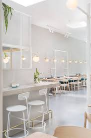light wood furniture. bar high stools tables wall bench banquette seating lighting white light soft green and grey pale wood furniture brass details