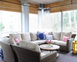 screened porch with woven wicker round coffee table navy blue and pink accents