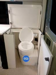 interior view of compartment doors open exposing the toilet in a sportsmobile conversion van
