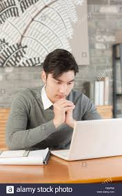 student sitting at desk hands folded.  Sitting Portrait Of Young Businessman Folding Hands And Looking Down In Cafe   Stock Image Intended Student Sitting At Desk Hands Folded F