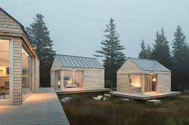 Three micro cabins, designed as summer guesthouses, on an island off the  coast of