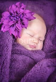 Closeup Portrait Of Cute Newborn Girl Sleeping Wrapped In Purple