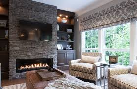 Grey stacked stone fireplace with tv above